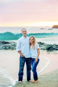 Beautiful couple standing on the beach at sunset Diver's cove