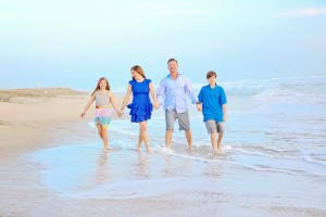 a-family-walking-through-water-in-Huntington-Beach