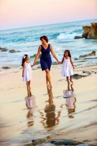 a-mom-walks-along-beach-talking-to-girls